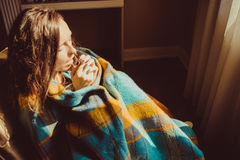 Winter cold concept. Young freezing woman in comfortable chair breathe warm air on frozen hands wrapped in warm fluffy woollen pla Stock Images