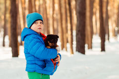 In the winter cold day warms boy puppy. Little boy wrapped the puppy in his jacket and warms it Stock Photos