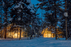 Winter cold night, small wooden houses with warm light Stock Photo