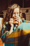 Winter cold sickness concept. Portrait Young freezing woman in comfortable chair with mug of tea wrapped in warm plaid blanket. Na Stock Image
