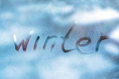 WINTER cold weather concept. Inscription word WINTER on the glass window with frozen patterns. WINTER cold weather concept. Inscription word WINTER on the blue stock photography