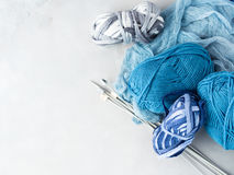 Winter color wool yarn with knitting needles. Space for text. Winter color wool yarn with knitting needles. Blue palette and gray clews. Gray background with Royalty Free Stock Images