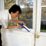 Winter is coming. Man do it yourself winterizing old house window and door with silicone sealant for winter to save money on heating and energy saving airtight Royalty Free Stock Photography