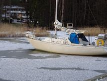A sailing boat has been forgotten in ice. Winter is coming and the owner has left the boat in bushes Stock Image