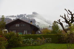 Winter is coming. A view of the hills near  La Maison du Gruyere at the beginning of winter during snowing. The mountings are covering with snow while lowland Stock Photo