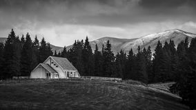 Winter is comming. Wooden house in the Romanian Carpathians, with mountains and snow in the background Stock Photography