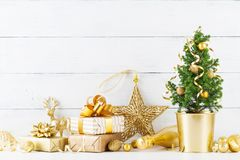 Winter composition with Christmas gift or present boxes, fir tree and golden holiday decorations on wooden background. stock photos