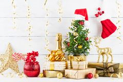 Winter composition with Christmas gift or present boxes, fir tree and golden holiday decorations on wooden background. royalty free stock images