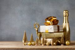 Winter composition with Christmas gift or present boxes and golden holiday decorations on wooden background. Greeting card. royalty free stock photo