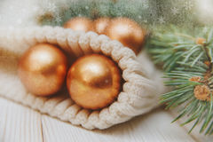 Winter composition with fir branches and golden balls on the white knitted hat stock photos