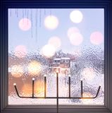 Lights on a frosted window. Winter composition with frosted window and lights. Christmas mood Royalty Free Stock Photography