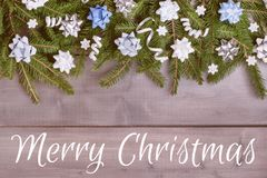 Winter composition with the inscription Merry Christmas. Spruce branches decorated with decorative bows, spirals of. Ribbons and white snowflakes, laid out on a stock image