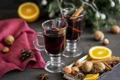 Mulled wine in glasses at black background. Fir wreath, tray with orange, cinnamon, nuts, cone and spices near. Winter composition. Mulled wine in glasses at stock photography