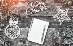 Winter composition, on old wood background. The space list for a Christmas message. Snow effect and light blips. royalty free stock photography