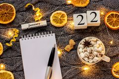 Winter composition. Wooden calendar January 22nd Cup of cocoa with marshmallow, empty open notepad with pen, dried oranges, light. Garland on grey knitted stock images
