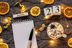 Winter composition. Wooden calendar January 23rd Cup of cocoa with marshmallow, empty open notepad with pen, dried oranges, light. Garland on grey knitted royalty free stock photos