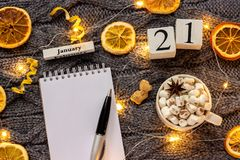 Winter composition. Wooden calendar January 21st Cup of cocoa with marshmallow, empty open notepad with pen, dried oranges, light. Garland on grey knitted stock photos