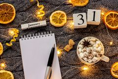 Winter composition. Wooden calendar January 31st Cup of cocoa with marshmallow, empty open notepad with pen, dried oranges, light. Garland on grey knitted stock image