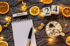 Winter composition. Wooden calendar January 24th Cup of cocoa with marshmallow, empty open notepad with pen, dried oranges, light. Garland on grey knitted royalty free stock photography