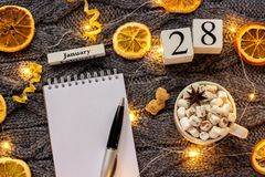 Winter composition. Wooden calendar January 28th Cup of cocoa with marshmallow, empty open notepad with pen, dried oranges, light. Garland on grey knitted royalty free stock image