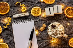 Winter composition. Wooden calendar January 11th Cup of cocoa with marshmallow, empty open notepad with pen, dried oranges, light. Garland on grey knitted royalty free stock image