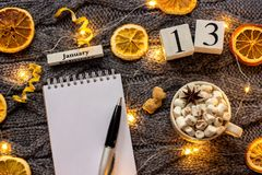 Winter composition. Wooden calendar January 13th Cup of cocoa with marshmallow, empty open notepad with pen, dried oranges, light. Garland on grey knitted stock photo