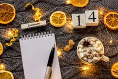 Winter composition. Wooden calendar January 14th Cup of cocoa with marshmallow, empty open notepad with pen, dried oranges, light. Garland on grey knitted stock image