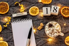 Winter composition. Wooden calendar January 18th Cup of cocoa with marshmallow, empty open notepad with pen, dried oranges, light. Garland on grey knitted stock image