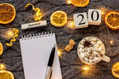Winter composition. Wooden calendar January 20th Cup of cocoa with marshmallow, empty open notepad with pen, dried oranges, light. Garland on grey knitted stock image