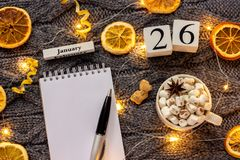 Winter composition. Wooden calendar January 26th Cup of cocoa with marshmallow, empty open notepad with pen, dried oranges, light. Garland on grey knitted stock photos