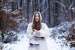 Winter concept. Beautiful girl in the winter forest in white down jacket. Joyful Beauty young woman Having Fun in Winter stock photos