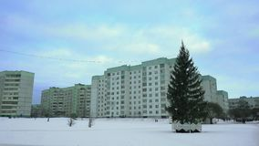 Decorated Christmas tree is in a poor residential area of the russian city on New Year`s Eve in the afternoon day. Winter. Concept of beginning of holidays and stock video footage