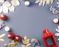 Winter concept flat lay with golden and silver leaves and red candles with snow falling. Christmas frame background royalty free stock images