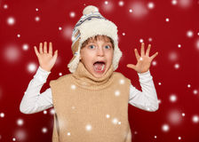 Winter concept - girl in hat and sweater open arms on red Royalty Free Stock Images