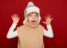 Winter concept - girl in hat and sweater open arms on red Stock Photos