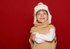 Winter concept - girl in hat and sweater posing on red background Royalty Free Stock Photo