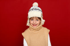 Winter concept - girl in hat and sweater posing on red background Stock Photo
