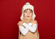 Winter concept - girl in hat and sweater on red background royalty free stock photo