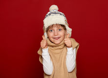 Winter concept - girl in hat and sweater show best gesture on red background Stock Photo