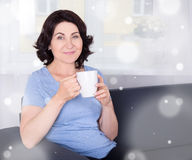 Winter concept -mature woman drinking coffee at home Stock Photography