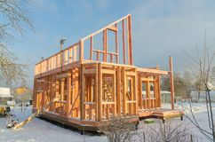 A construction of frame wooden house on pile Foundation in winter. The winter, the construction of a frame wooden house on a pile Foundation royalty free stock image