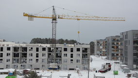 Winter construction site with cranes and workers building house stock video