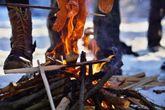 Winter cookout with sausages above the fire placed on snow Royalty Free Stock Photography