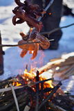 Winter cookout with sausages above the fire placed on snow Royalty Free Stock Photo