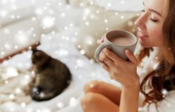 Close up of happy woman with cup of cocoa at home. Winter, cosiness, leisure and people concept - close up of happy young woman with cup of coffee or cacao and royalty free stock photos