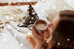 Close up of happy woman with cup of cocoa at home. Winter, cosiness, leisure and people concept - close up of happy young woman with cup of coffee or cacao and stock photos