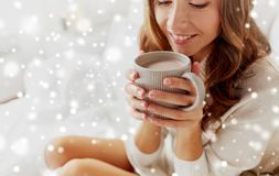 Close up of happy woman with cup of cocoa at home. Winter, cosiness, leisure and people concept - close up of happy young woman with cup of coffee or cacao at royalty free stock photography