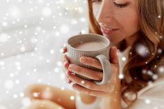 Close up of happy woman with cup of cocoa at home. Winter, cosiness, leisure and people concept - close up of happy young woman with cup of coffee or cacao over royalty free stock image