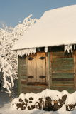 Winter cottage. Snow cover the village, frozen trees and bushes, small timber house in snow Stock Image