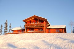 Winter cottage. Orange wooden cottage in a winter landscape Stock Images